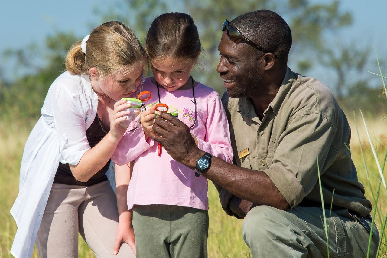 Guide shows young kids how to recognize certain insects in the Okavango Delta